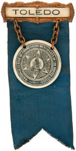 RARE TWO PART CELLULOID BADGE ISSUED FOR THE FIRST ORGANIZATION OF THE FRUIT AND VEGETABLE INDUSTRY.
